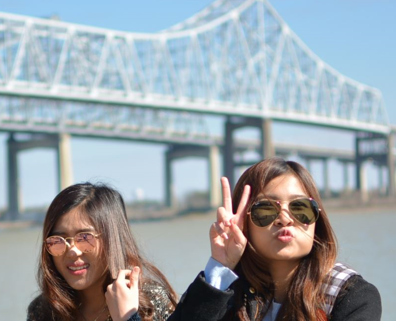 Women posing with peace sign and silly faces in front of Crescent City Connection Bridge