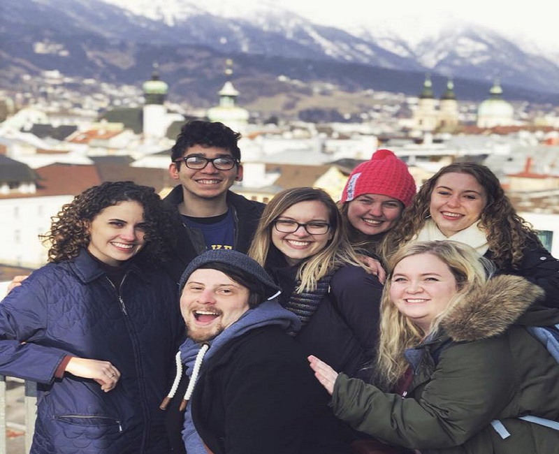 group of students posing in front of mountains in austria