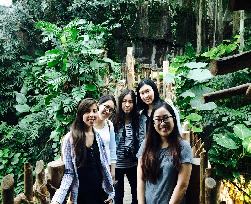 Students standing in front of jungle foliage at the Aquarium