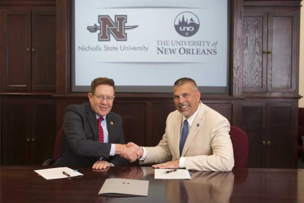 Nicholls State President Jay Clune and UNO President John Nicklow finalize a memorandum of understanding between the two universities at a signing ceremony on the Nicholls campus.